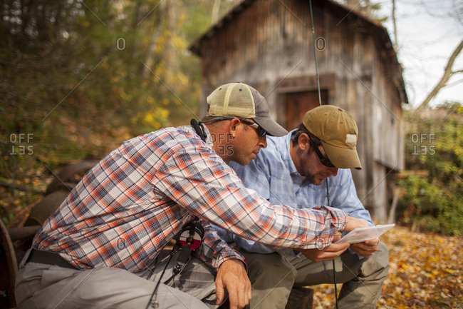 Men holding fishing rods and box by log cabin
