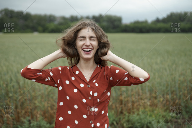 Laughing woman wearing red polka dot shirt in wheat field