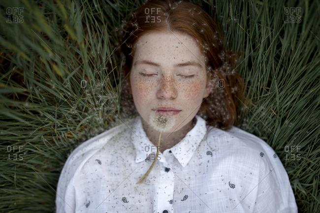 Teenage girl lying down with dandelion seed head