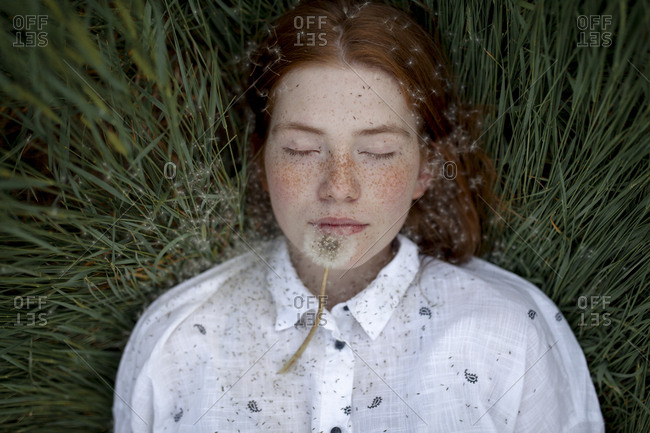 Teenage girl lying down with dandelion seed head