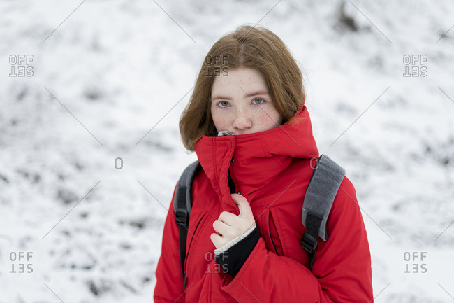 Teenage girl wearing red coat in snow