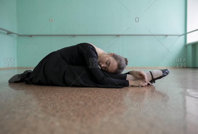 Ballet dancer wearing black dress stretching in studio