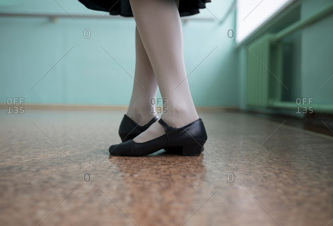 Feet of ballet dancer wearing black shoes