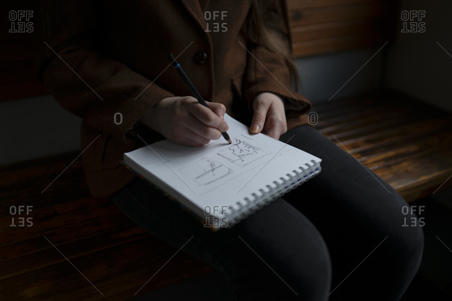 Woman drawing in note pad on train