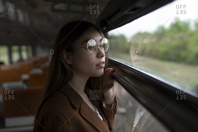 Young woman wearing glasses looking out of train window