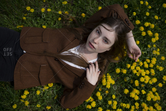 Young woman wearing brown blazer lying on yellow flowers