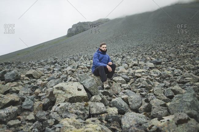 Young man sitting on rock hill in Kirkjub�jarklaustur, Iceland