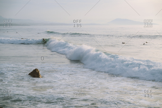 Surfer riding a wave in French coast during a hazy sunset