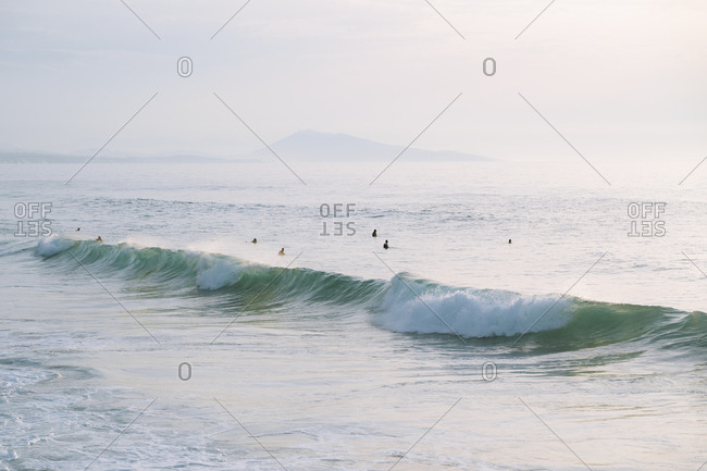 Surfers enjoying an autumn dip in the beach during sunset
