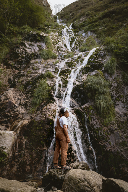 Young male hiker in sandals exploring hidden waterfalls