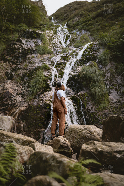 hiker, waterfall, hiking, vacation, lifestyle, crouching, rock formation, nature, getaway, water, adventure, flowing water, rocks, remote, destinations, casual clothing, holding, flowing, motion, exploration, environment, day, outdoors, one person, 26-29 years old, millennial, young adult, young man, young male, male, caucasian ethnicity, basque country, spain, tourism, destination, travel, explorer, trekking, sandals, long hair, autumn, fall