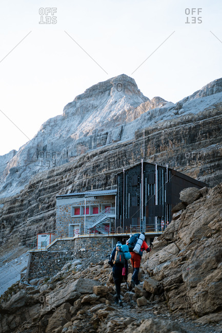 Two male hikers arriving in Roland mountain hut in French Pyrenees