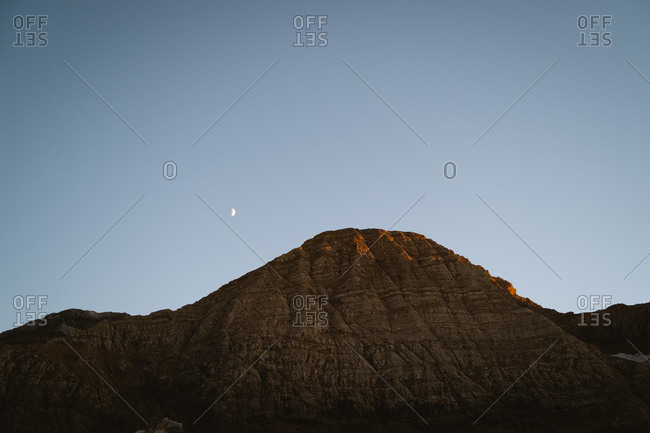 Sunset golden light hitting the hills of a big mountain in Pyrenees with the moon in the sky