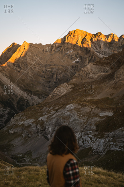 Long haired man wearing brown vest watching the sunset light hitting mountain peaks in Pyrenees