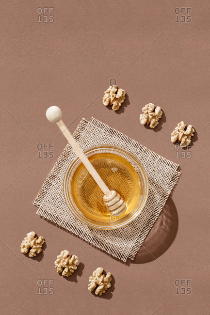 orderly composition with honey and walnuts on a brown background