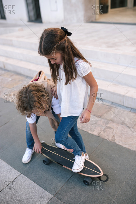 Boy teaching girl how to ride a skateboard