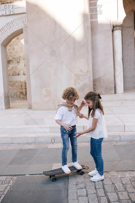 Girl teaching boy how to ride a skateboard