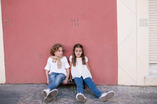 Two kids sitting side by side on a skateboard