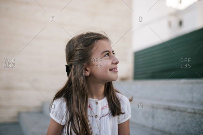 Caucasian girl smiling while on cement stairs