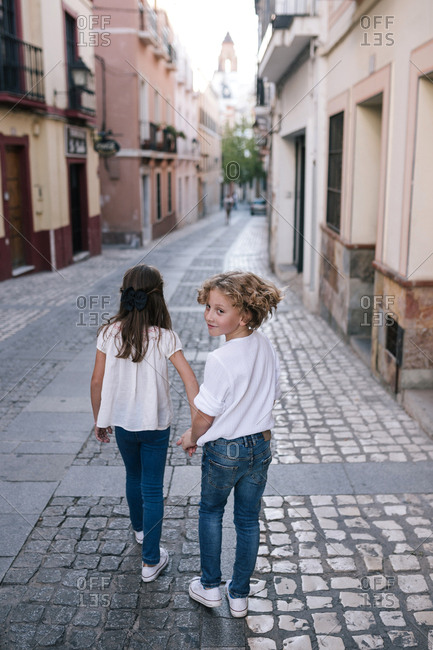 Girl and boy walking through the city holding hands while boy looks over shoulder