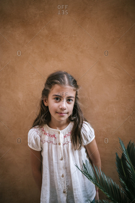 Portrait of Caucasian girl next to a plant