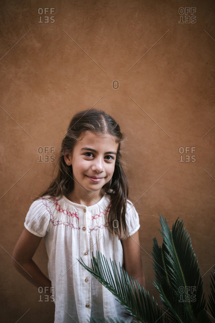 Portrait of smiling Caucasian girl next to a plant