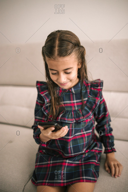 Caucasian girl looking at a mobile phone while sitting on sofa