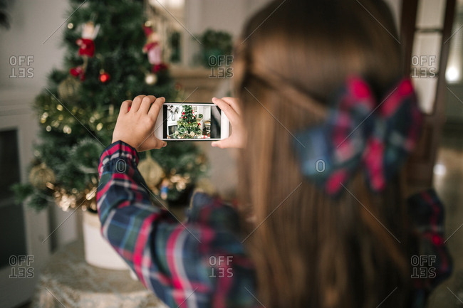 Girl taking a picture with mobile phone of a Christmas tree