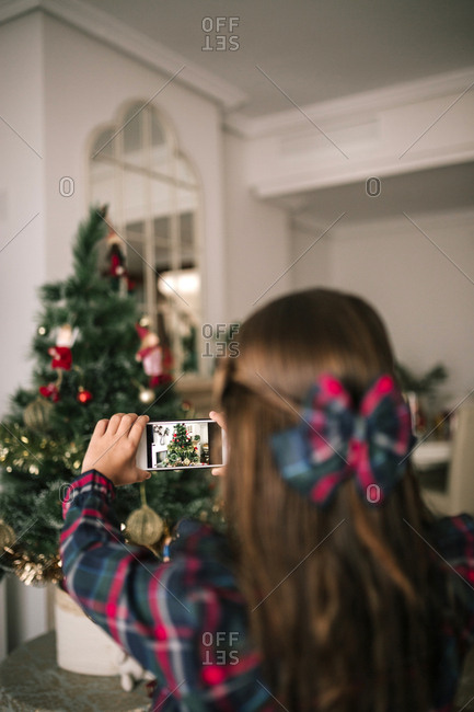 View over shoulder of girl taking a picture with phone of a Christmas tree