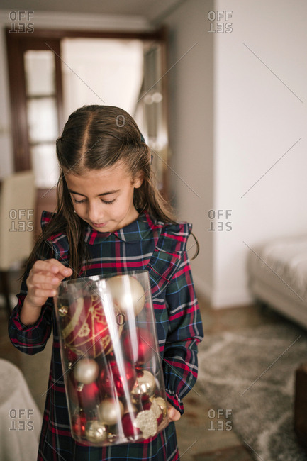 Girl decorating the Christmas tree with red and golden ornaments