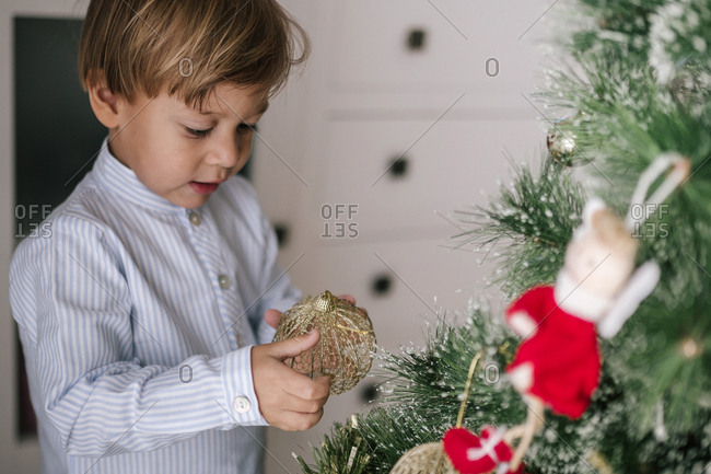 Caucasian boy with blond hair decorating a Christmas tree