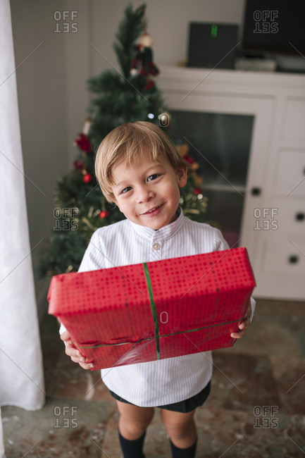 Happy little boy with Christmas gift in hands