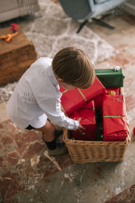 Caucasian boy looking at Christmas presents in a basket