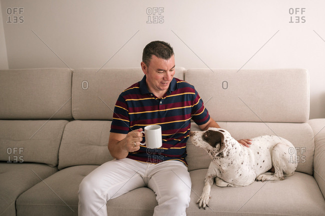Caucasian man with cup of coffee sitting in the armchair with his dog