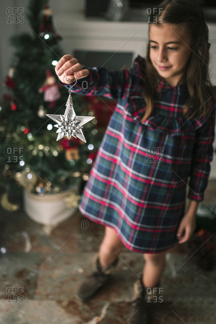 Caucasian girl decorating the Christmas tree with a glass star