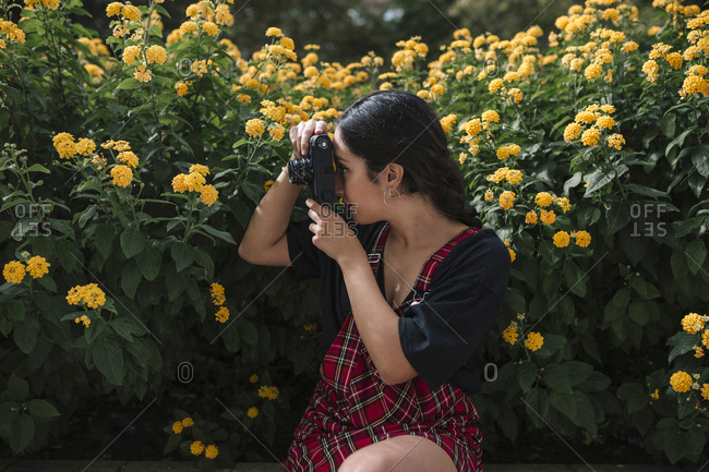 Young woman photographing yellow flowers