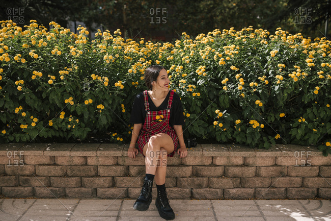 Teen girl sitting by yellow flowers in a park in a city of Spain