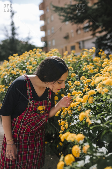 Teen girl smelling yellow flowers in a park in a city of Spain