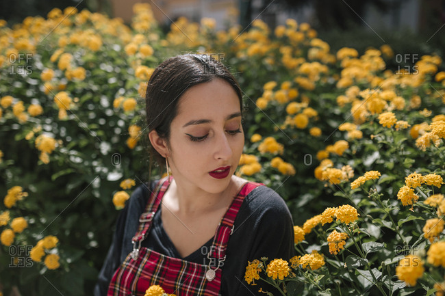 Young woman smelling yellow flowers in a park in a city in Spain