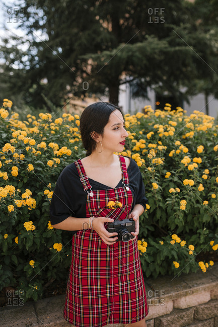 Teen girl holding camera in a park with yellow flowers