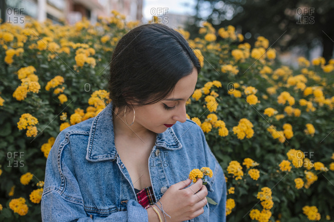 Teen girl placing yellow flowers in her pocket at a city park