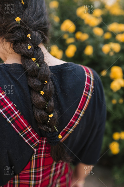 Rear view of girl with yellow flowers in the braid of her hair