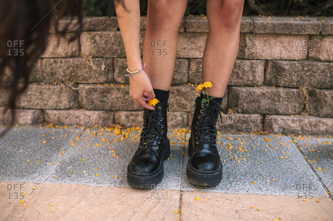 Teenage girl placing yellow flowers inside her boots