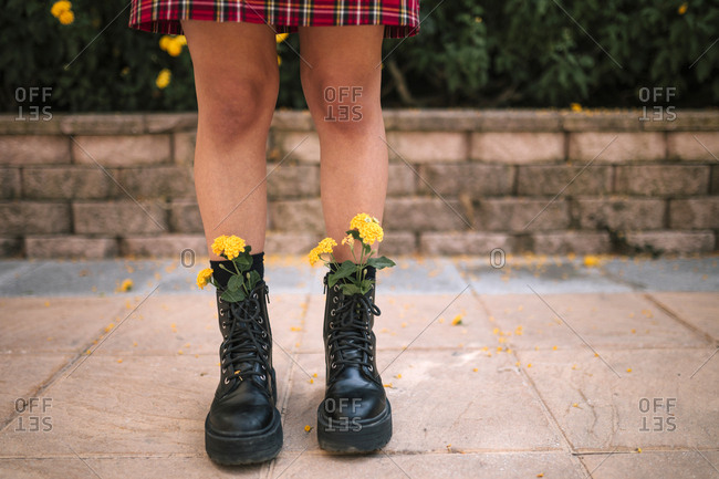 Yellow flowers inside a teenage girl's boots