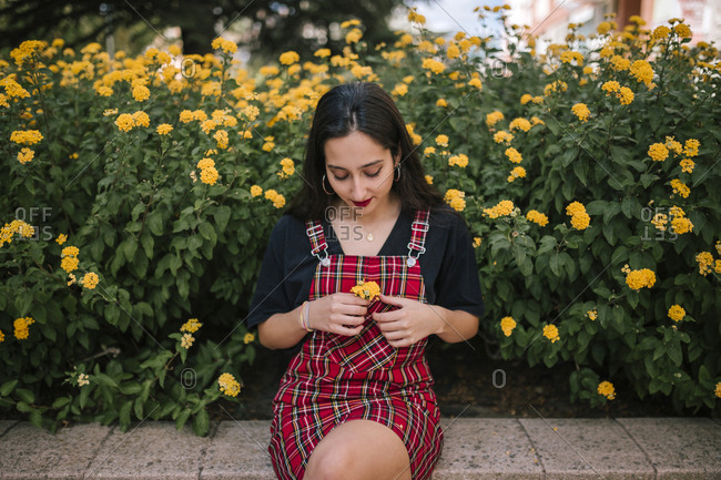 Teen girl placing yellow flowers in her pocket while sitting in a city park