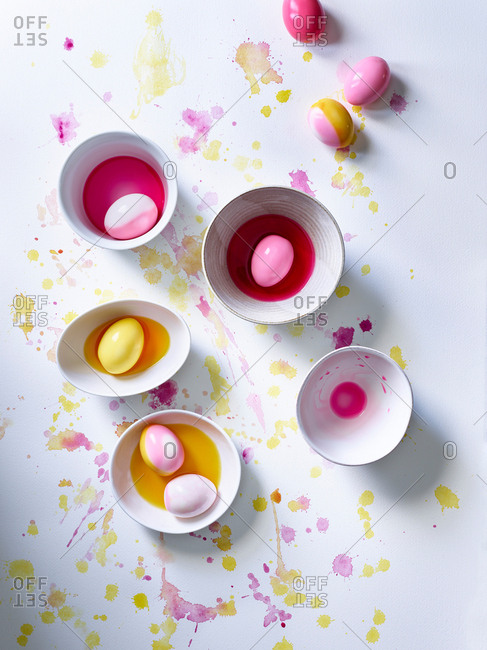 Pastel pink and yellow dyes on white surface with eggs