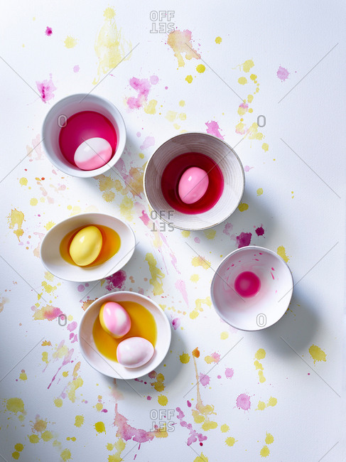 Overhead view of pastel pink and yellow dyes on white surface with eggs