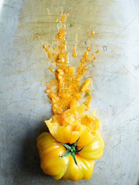 Overhead view of a splattered yellow tomato