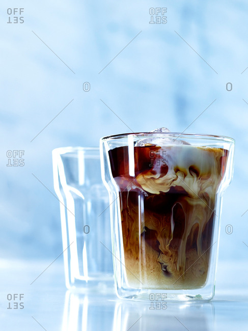 Glass filled with iced coffee and creamy milk