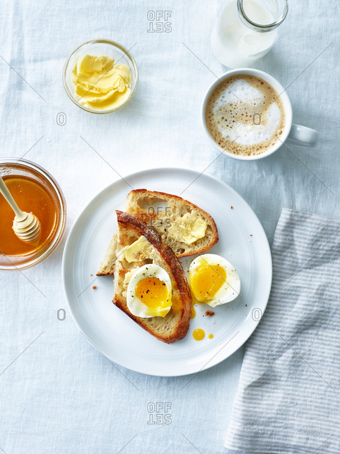 Overhead view of breakfast with toast and soft boiled eggs served with coffee